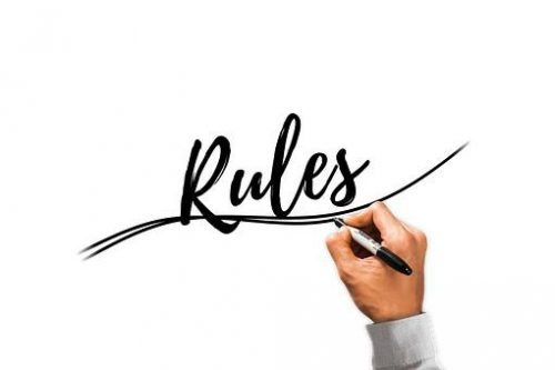"Man's hand writing ""Rules"""