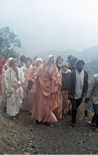 Swami Satchidananda walking with devotees