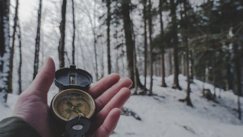 compass in man's hand in snowy woods
