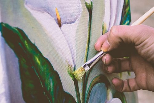 Artist holding paintbrush on floral painting