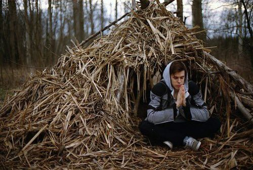 Man in a primitive thatched hut having his best day