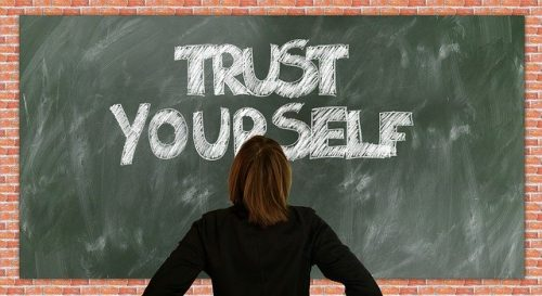 Trust Yourself on blackboard with woman in front