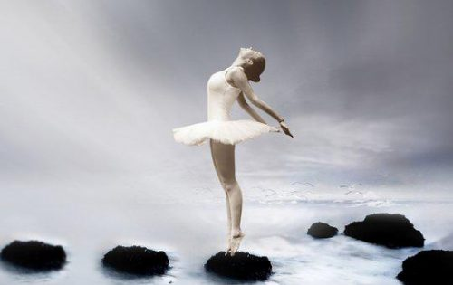 Ballerina on ocean rocks