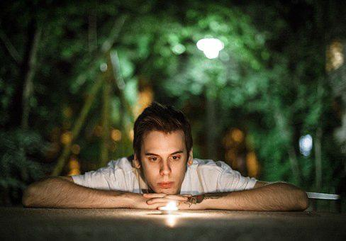 Young man gazing at a volitive candle