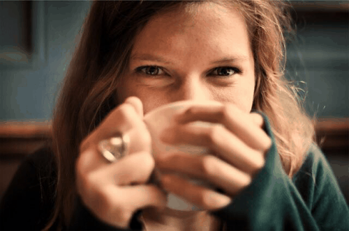 Woman embracing a coffee cup