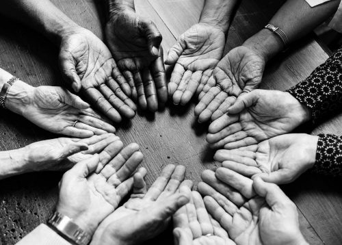 a circle of open hands showing common ground