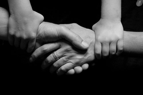 4 connected hands in an embrace
