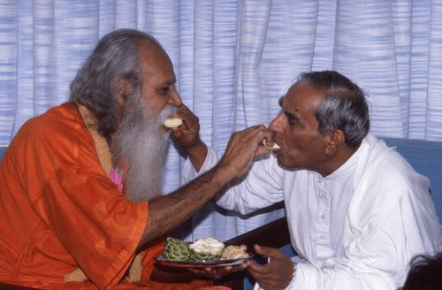 Dada and Swami Satchidananda feeding each other