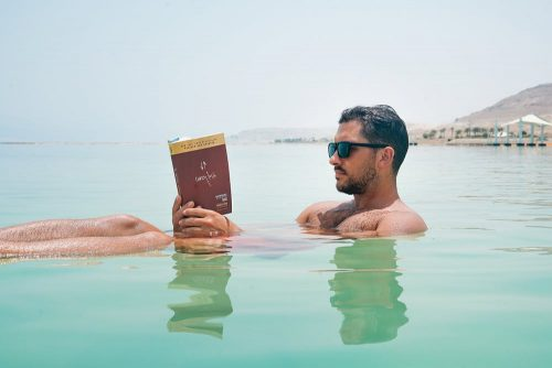 Man reading book floating on the dead sea