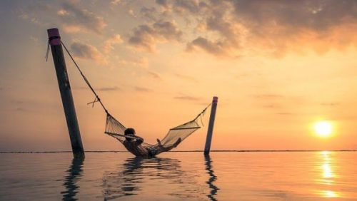 man in hammock over ocean at high tide