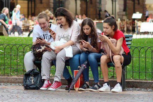 4 kids busy using smart phones