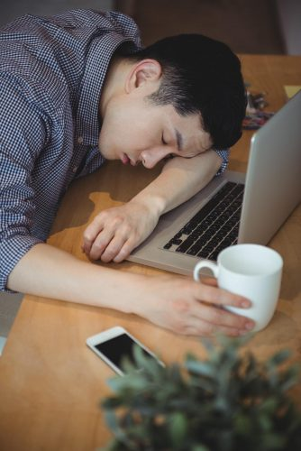 Fatigued man sleeping near a laptop