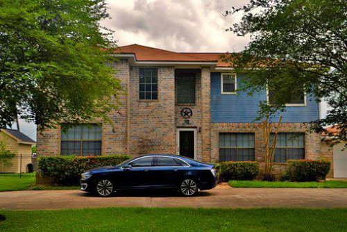 Luxury car parked in front of a mansion
