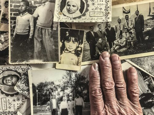 elder's hand on old photos
