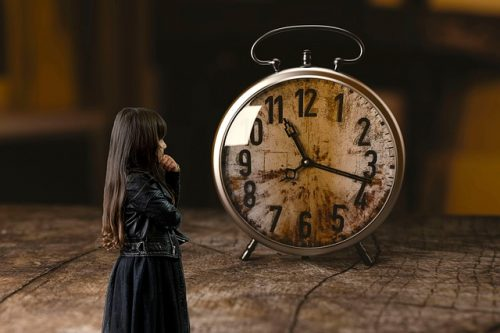 girl looking at old clock