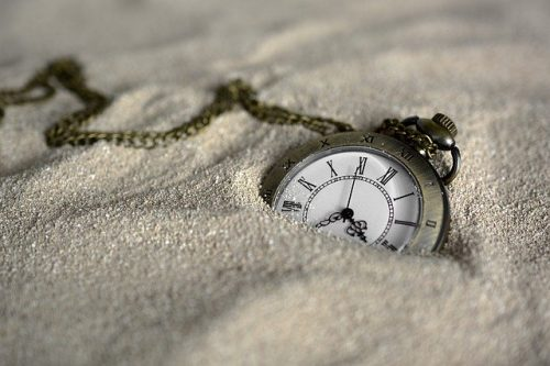 pocket watch half buried in sand