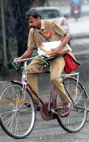 Postal carrier on a bicycle, holding mail