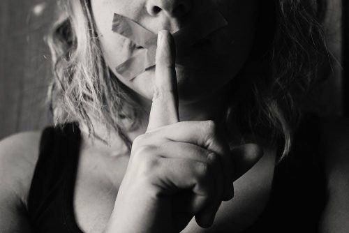 Woman with taped mouth and finger showing secret kept