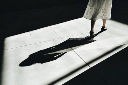 woman walking away from her shadow