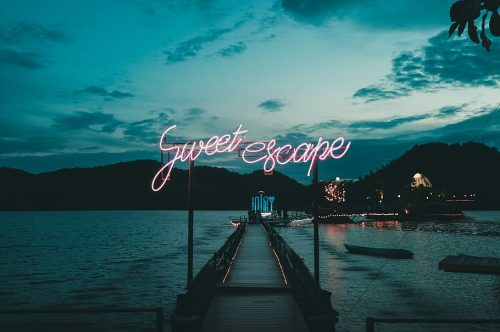 Sweet Escape neon sign on a dock