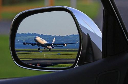 Airplane take-off reflected in auto's side mirror.