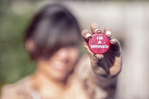 I am a winner button held by a woman.