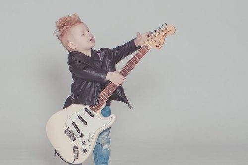 Young, redhead boy tuning a big electric guitar.